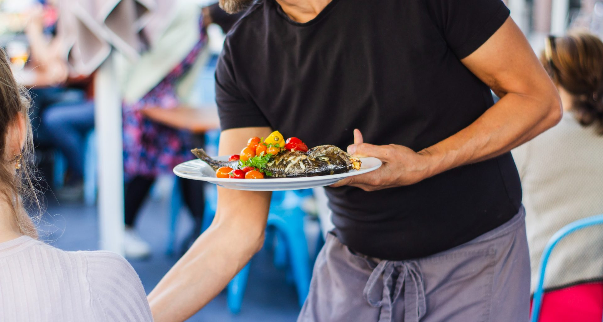 a food runner is delivering food to customers' table