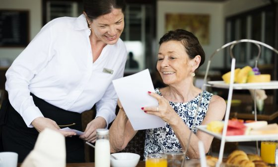 a waitress is making recommendations for restaurant guests